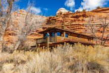 USA, Utah, Escalante, Woman On Deck Of Home In Canyon In Grand Staircase-Escalante National Monument