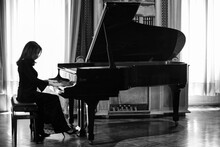 An Elegant Female Pianist Plays A Grand Piano. Black And White Photo Of A Young Musician In A Long Black Dress. Classical Music, Opera And Italian Culture. Hands On Piano Keys.