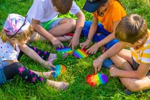 Children Play Pop It On The Street. Selective Focus.