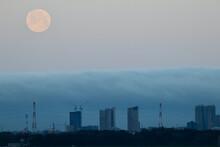 低い雲に包まれた高層ビルと満月