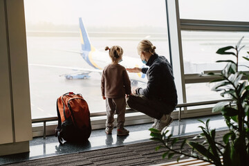 Man with girl ready to fly by airplane and the airport. Father and child looking though the lounge window on plane with backpack. Copy space, safe family travel in face mask during Covid-19 quarantine