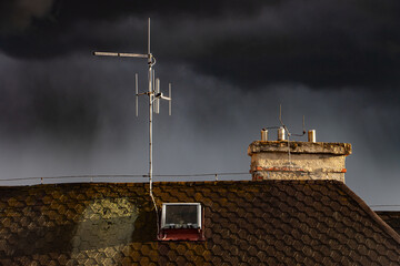 Dark sky with rain clouds over the roof of the house with an antenna