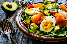 Salmon Salad - Smoked Salmon, Hard Boiled Eggs, Avocado And Green Vegetables On Wooden Table