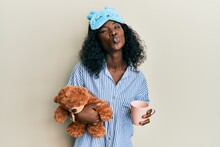 Beautiful African Young Woman Wearing Pajama, Holding Teddy Bear And Drinking Coffee Looking At The Camera Blowing A Kiss Being Lovely And Sexy. Love Expression.