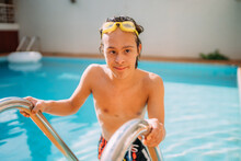 Latino Down Syndrome Boy Swimming In The Pool. Disabled Brazilian.