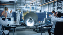 Technician In Protective Suit Finishes Satellite Construction, Team Of Scientists Applaud And Cheer For Successful. Aerospace Agency Manufacturing Facility: Scientists Assembling Spacecraft.