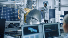 Managing Engineer And Chief Technician Working On Satellite Construction, Talk, Use Computer. Aerospace Agency Manufacturing Facility: Scientists Assemble Spacecraft For Space Exploration Mission