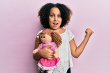 Young Little Girl With Afro Hair Holding Animal Doll Toy Pointing Thumb Up To The Side Smiling Happy With Open Mouth