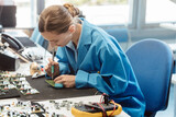 Worker in electronics manufacturing soldering a component