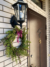 Decorative Wreath Of Fresh Twigs, Sage Flowers And Leaves With A Purple Ribbon Hangs Against The Background Of A Light Cypress Wall Next To The Front Door To The House.