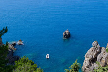 Small Inflatable Boat In The Sea At The Rocky Coast Of Corfu, Greece.