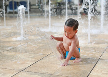 Funny Little Asian Baby Boy Having Fun On Water Stream Of A Sprinkler. Kid Playing In Playground Fountain In Aqua Park.