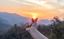 Silhouette Of Female Hand Holding Sun.