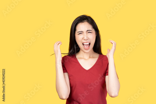 Obraz na plátně Young Asian woman wearing red t-shirt over yellow background