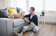 Portrait Of Disabled Young Man Playing With Dog Indoors At Home, Leg Prosthetic Concept.