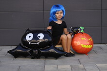Little Beautiful Girl In A Blue Wig Sits With A Balloon In The Form Of A Bat Isolated On A Black Wall. Funny Child In Carnival Costumes Celebrating Halloween Outdoors.