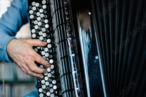 Fotografie, Obraz Detail of a musician's hand playing the accordion.