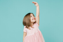 Little Fun Kid Girl 5-6 Years Old Wears Pink Dress Hold Hand Above Head Show How Much She Grown Try To Be Taller Isolated On Pastel Blue Color Background Child Studio Mother's Day Love Family Concept