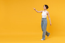 Full Length Side View Young Woman 20s With Bob Haircut Wear White Tank Top Shirt Walking Go Point Index Finger Aside On Workspace Area Mock Up Isolated On Yellow Background People Lifestyle Concept