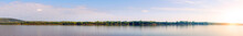 Panorama Of A Large River With A Sandy Bank Against A Cloudy Sky In The Evening