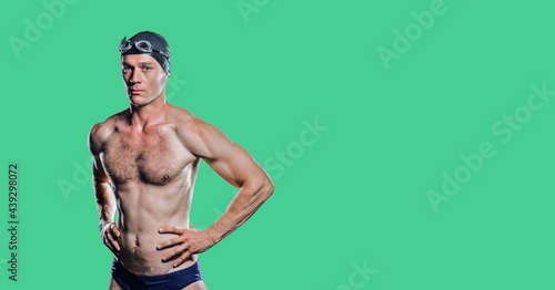Composition of male swimmer with copy space isolated on green background