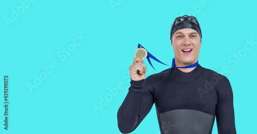 Composition of smiling male swimmer holding medal with copy space isolated on blue background