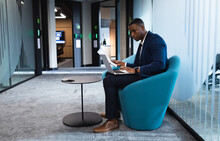 African American Businessman Holding A Document Using Laptop While Sitting On Chair At Modern Office
