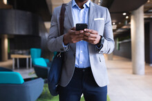 Mid Section Of African American Businessman Using Smartphone While Standing At Modern Office