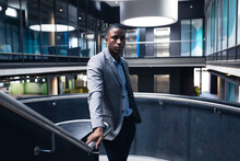 Portrait Of African American Businessman Standing On The Stairs At Modern Office