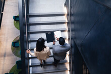 Diverse Businessman And Businesswoman Discussing Together Standing On The Stairs At Office