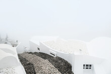 White Architecture On Santorini Island, Greece. Misty Morning With Heavy Fog. White Roofs Of The Houses And Stairs Down To The Sea