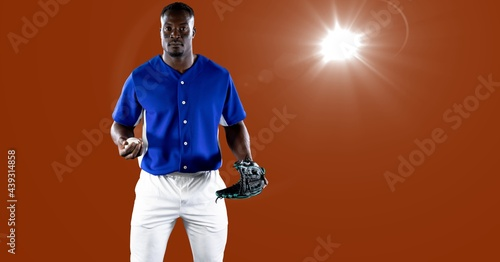 African american male baseball pitcher holding a ball against spot of light on orange background