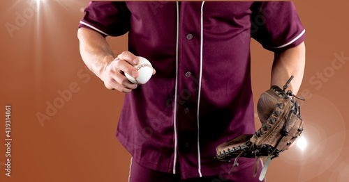 Mid section of male baseball pitcher holding a ball against spot of light on orange background
