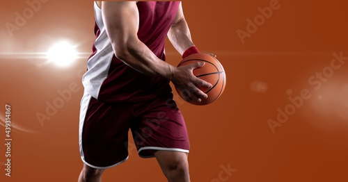Mid section of male basketball player holding basketball against spot of light on orange background