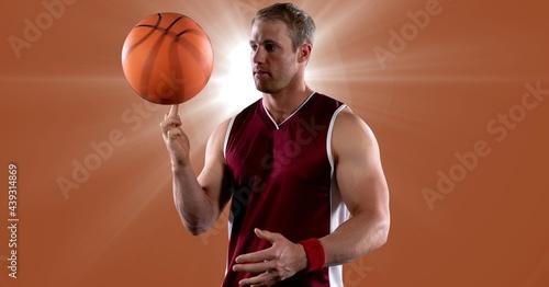 Caucasian male basketball player spinning basketball against spot of light on orange background