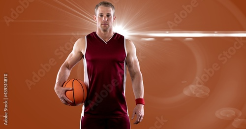 Portrait of caucasian male basketball player holding basketball against spot of light in background