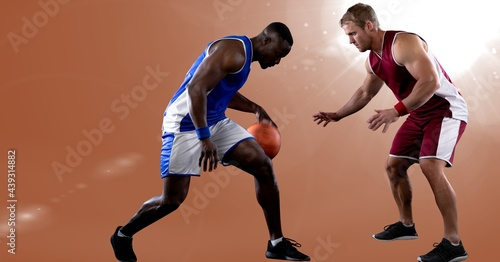Two diverse male basketball players playing basketball against spot of light in background