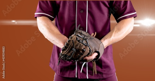 Mid section of male baseball pitcher wearing gloves against spot of light on orange background