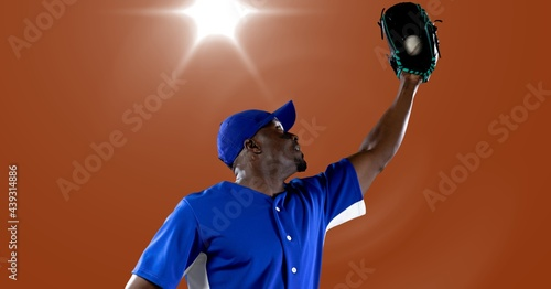 African american male baseball player catching a ball against spot of light in background