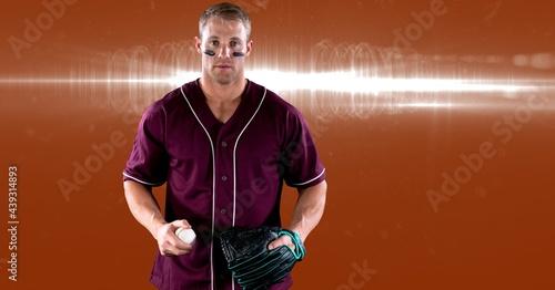 Portrait of caucasian male baseball pitcher holding ball against spot of light on orange background