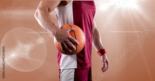 Mid section of male basketball player holding basketball against spot of light in background