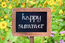 Happy Summer Sign Written On A Vintage Wooden Frame Chalkboard, Flower In The Background