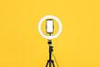 Leinwandbild Motiv Modern tripod with ring light and smartphone on yellow background