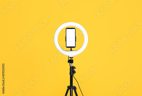 Carta da parati Modern tripod with ring light and smartphone on yellow background