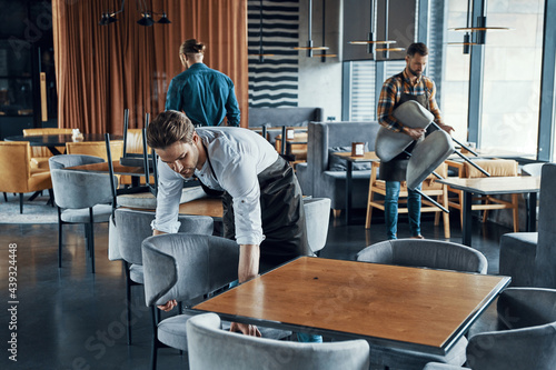 Handsome young men in aprons arranging furniture while preparing restaurant to opening