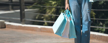 Shopper Asian Woman Holding Shopping Bags At Outdoor Area On Day Banner Size Background.