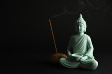 Beautiful Ceramic Buddha Sculpture With Burning Candle And Incense Stick On Black Background. Space For Text