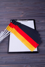 Vertical Shot Collection Of Germany Flags And Clipboard With Paper.