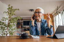 Senior Woman, Talking Over The Phone, At Her Home Office.
