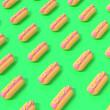 Leinwandbild Motiv 3D render of pattern of hot dogs with mustard on green background. Creative concept.